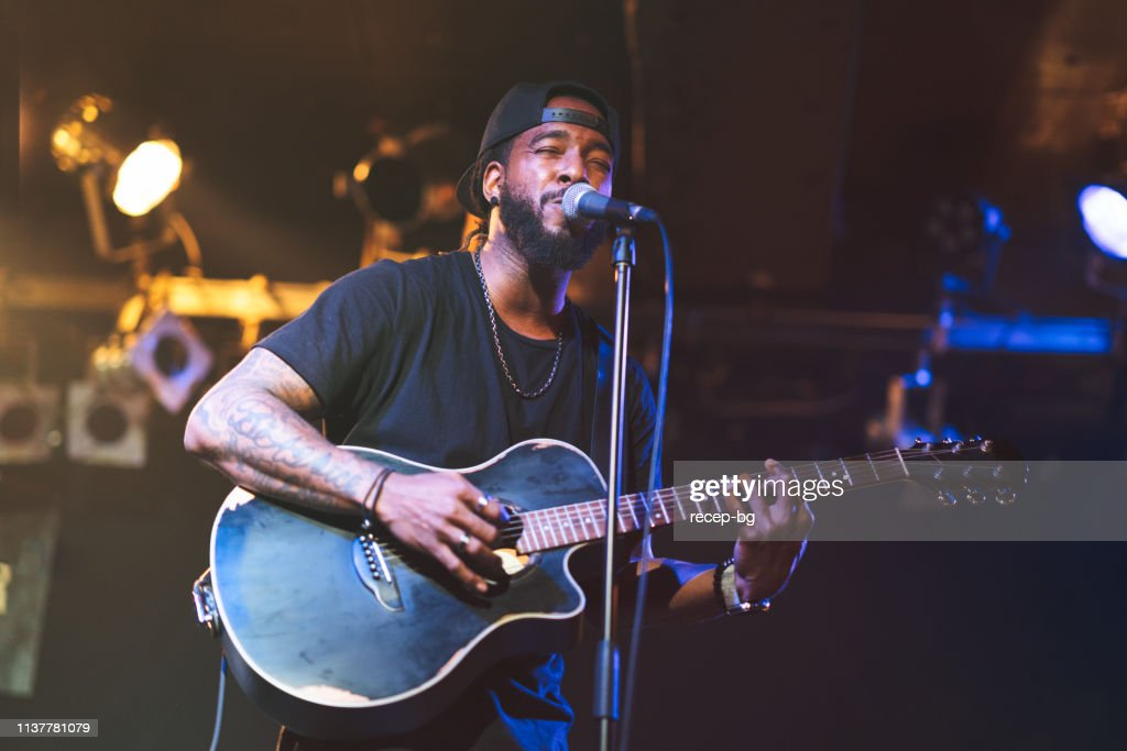 Black man playing acoustic guitar and singing on stage : Stock Photo