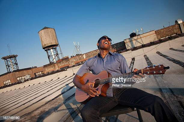 Black man playing guitar on rooftop