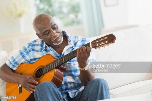 black man playing guitar on sofa - activité de loisirs photos et images de collection