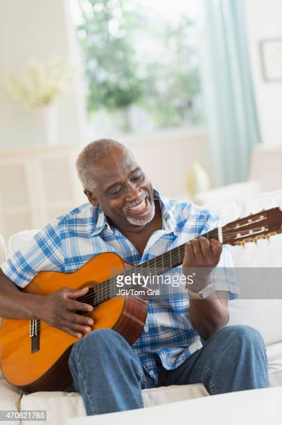 Black man playing guitar on sofa