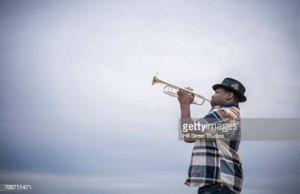 black man playing trumpet under clouds - trumpet stock pictures, royalty-free photos & images