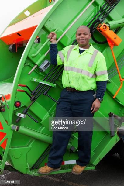 Black man riding on back of garbage truck