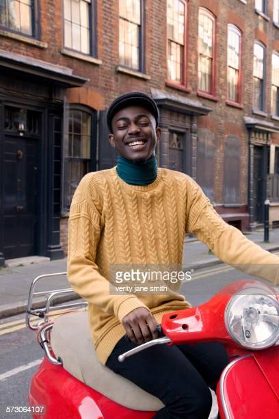 Black man riding scooter on urban street