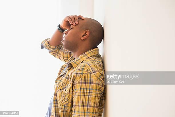 Black man rubbing his forehead