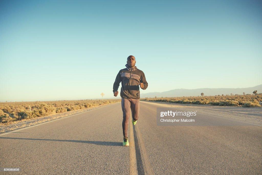 black man running along highway ストックフォト getty images