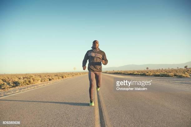 Black man running along highway