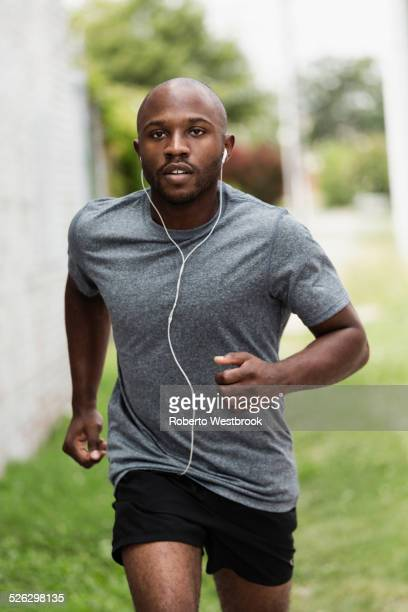Black man running in urban grass