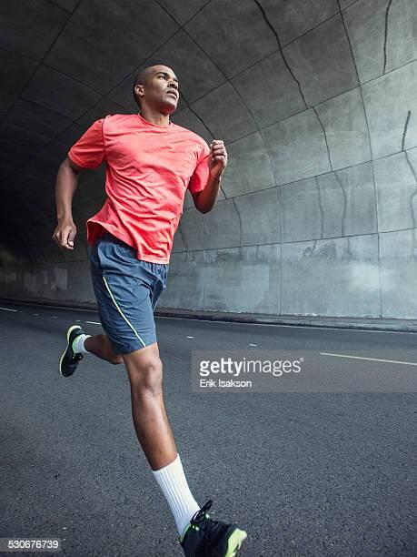 Black man running in urban tunnel