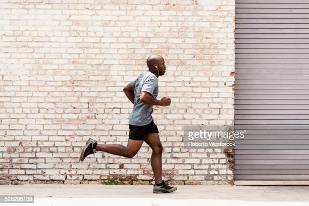 Black man running on city sidewalk