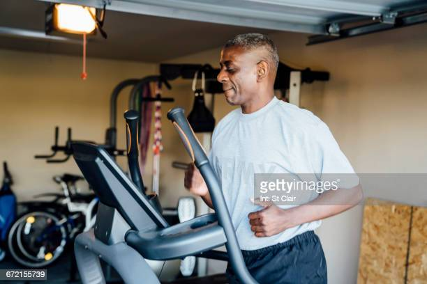 black man running on treadmill in garage - cardiovascular exercise stock pictures, royalty-free photos & images