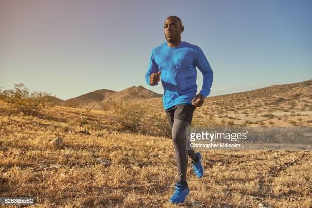 Black man runs across hills