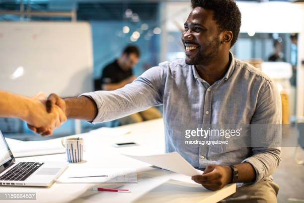 black man shaking hands with unrecognizable person at work - all shirts stock pictures, royalty-free photos & images