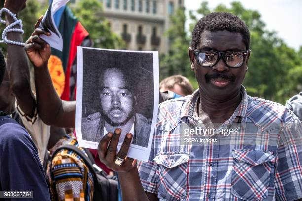 Black man shows the portrait of a person who died because of immigration laws. More than 3,000 people have demonstrated in the center of Barcelona to...