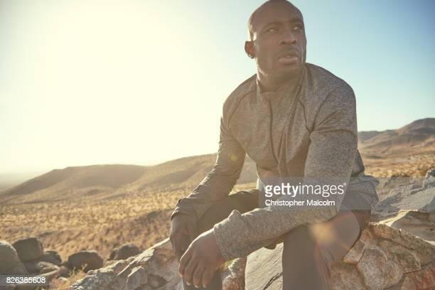 Black man sits on rocks on hill mountain