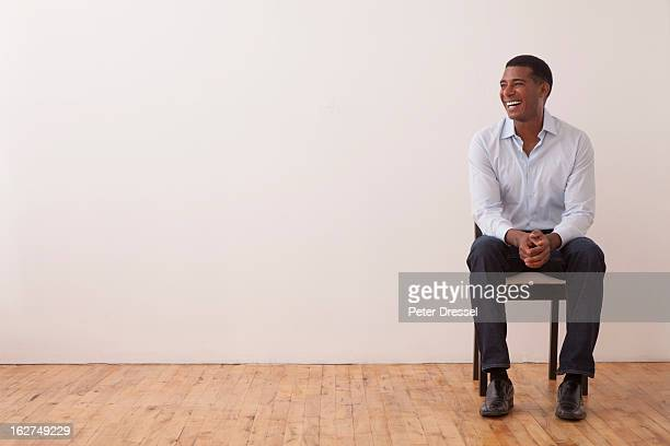 black man sitting in chair - sitting foto e immagini stock