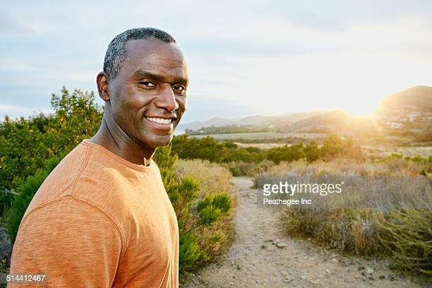 Black man smiling on rural hillside