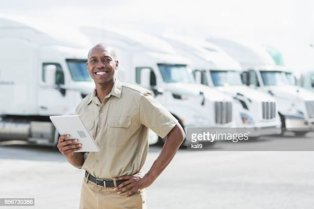 black man standing in front of semi-trucks - heavy industry stock photos and pictures