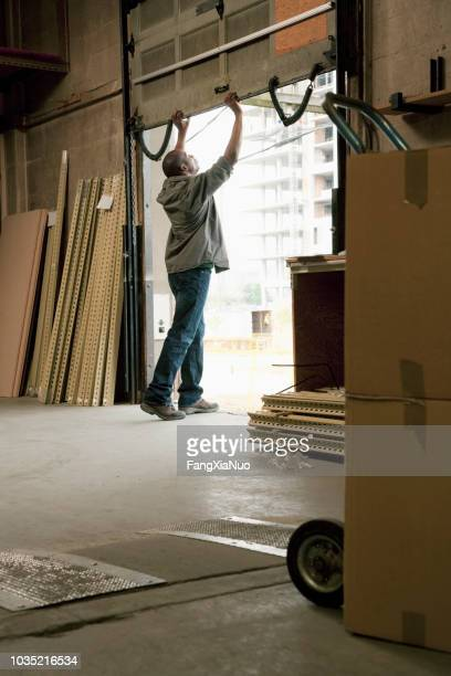 black man standing on warehouse loading dock - industrial door stock pictures, royalty-free photos & images