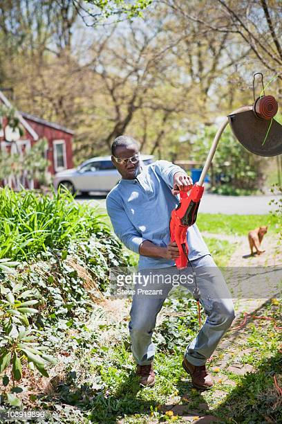 Black man struggling with weed trimmer