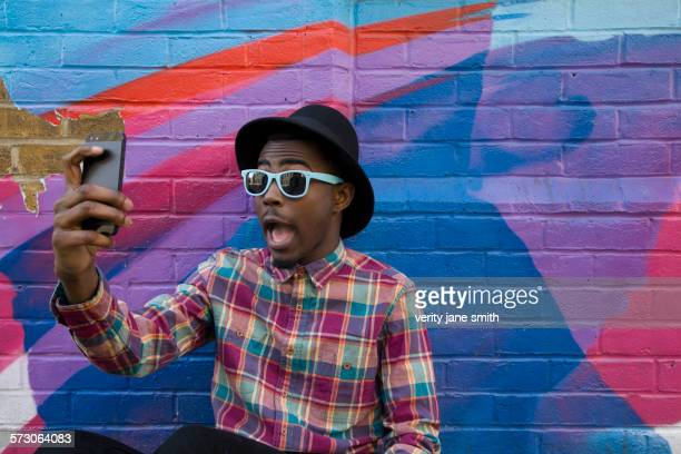 black man taking selfie near colorful wall - hi tech moda stock pictures, royalty-free photos & images