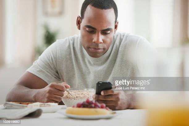 Black man text messaging and eating breakfast