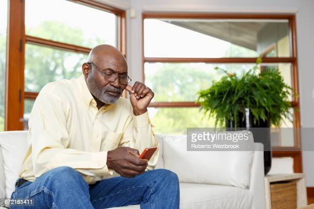 Black man texting with cell phone on sofa
