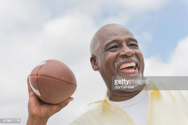black man throwing football outdoors - old american football stock photos and pictures