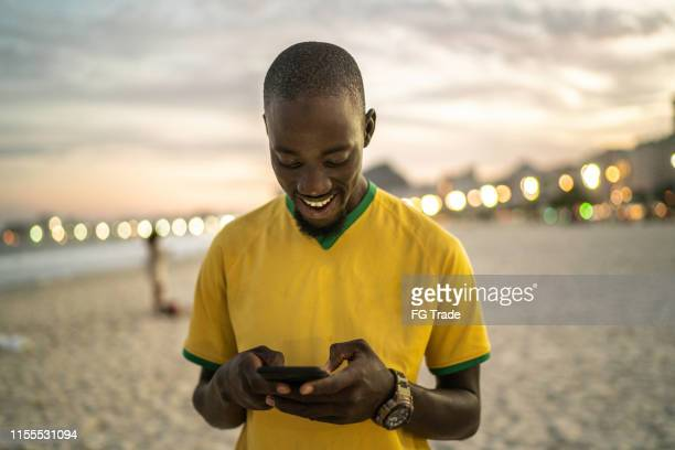 black man typing a message at the beach - brazil stock pictures, royalty-free photos & images