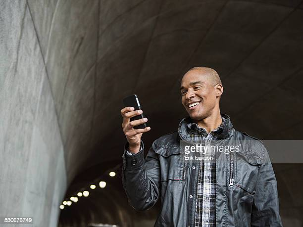 Black man using cell phone in urban tunnel