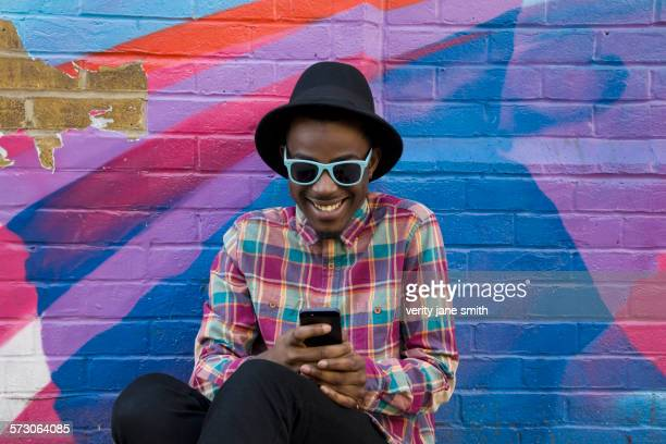 black man using cell phone near colorful wall - multi colored hat stock pictures, royalty-free photos & images