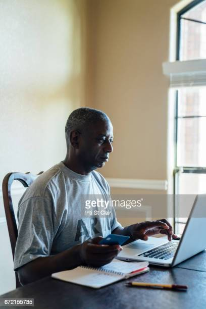Black man using credit card with laptop at table