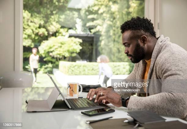 black man using digital tablet working from home - 在宅勤務 ストックフォトと画像