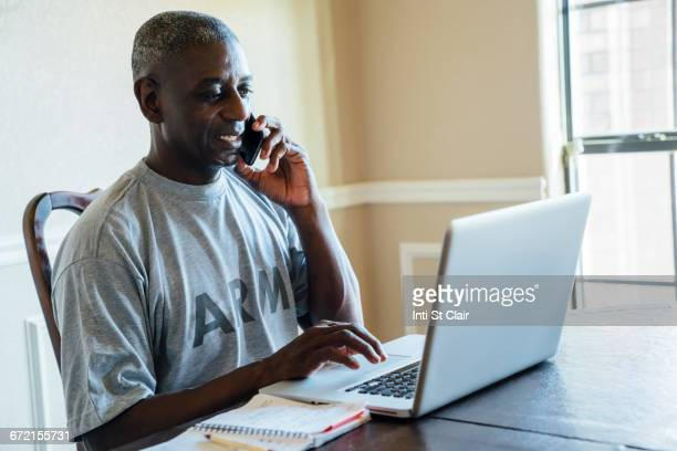 Black man using laptop and cell phone at table