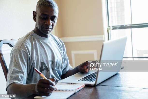 black man using laptop and notebook at table - war veteran stock pictures, royalty-free photos & images