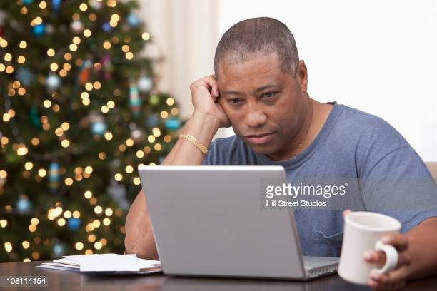 Black man using laptop with Christmas tree in background