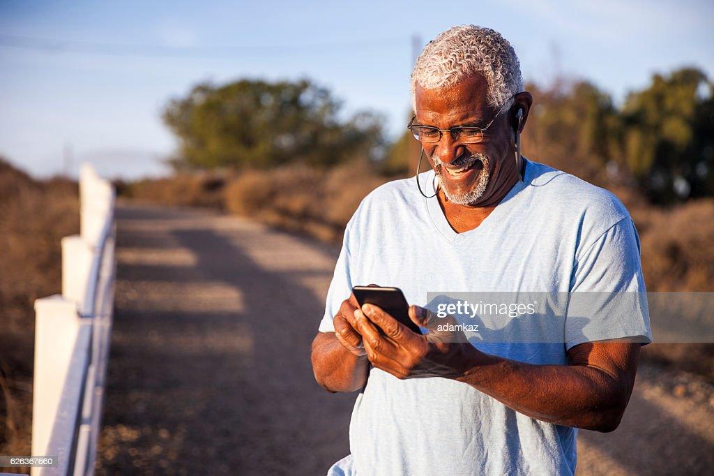 Black Man using smartphone on mountain trail : Stock Photo