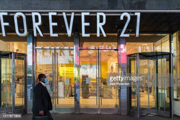 black man wearing a protective mask walking in front of closed forever 21 department store in times square during the covid-19 pandemic. - alex potemkin coronavirus stock pictures, royalty-free photos & images