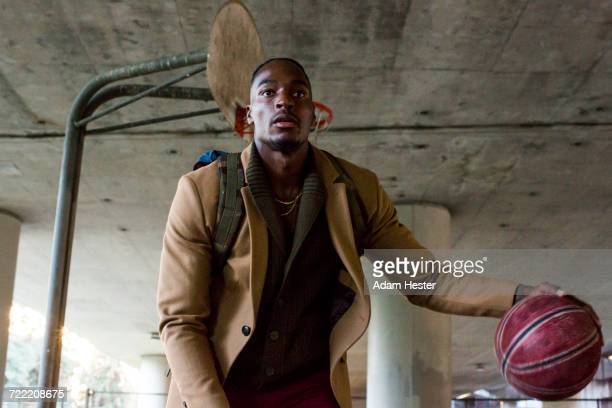 black man wearing backpack playing basketball under overpass - stipendium stock-fotos und bilder
