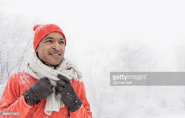 black man wearing gloves and scarf in snow - black glove stock pictures, royalty-free photos & images