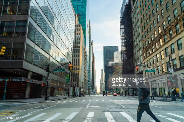 a black man wearing protective mask man crossing 6th avenue of americas in midtown manhattan deserted because of the city lockdown caused by covid-19 pandemic. - alex potemkin coronavirus stock pictures, royalty-free photos & images