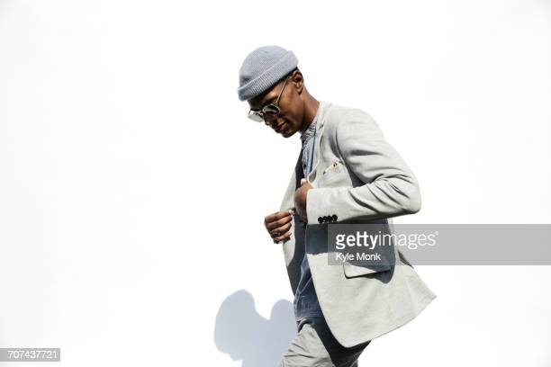 black man wearing sunglasses adjusting jacket - fashion stock-fotos und bilder