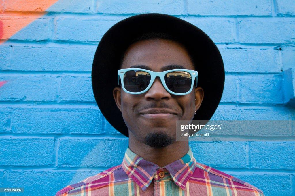 Black man wearing sunglasses near colorful wall : Stock-Foto