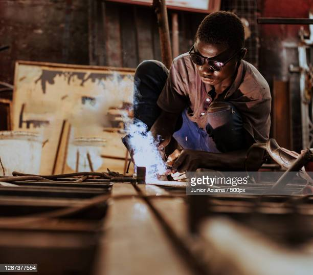 black man welding outdoors, tema, ghana - manufacturing stock pictures, royalty-free photos & images