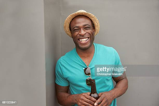 black man with bottle laughing - only young men stock pictures, royalty-free photos & images