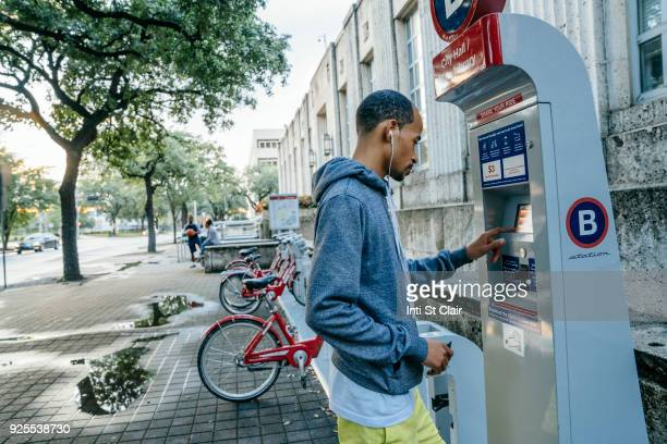 black man with earbuds paying for bicycle rental with credit card - charging sports stock pictures, royalty-free photos & images