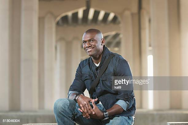Black man with shaved head wearing jewelry and denim