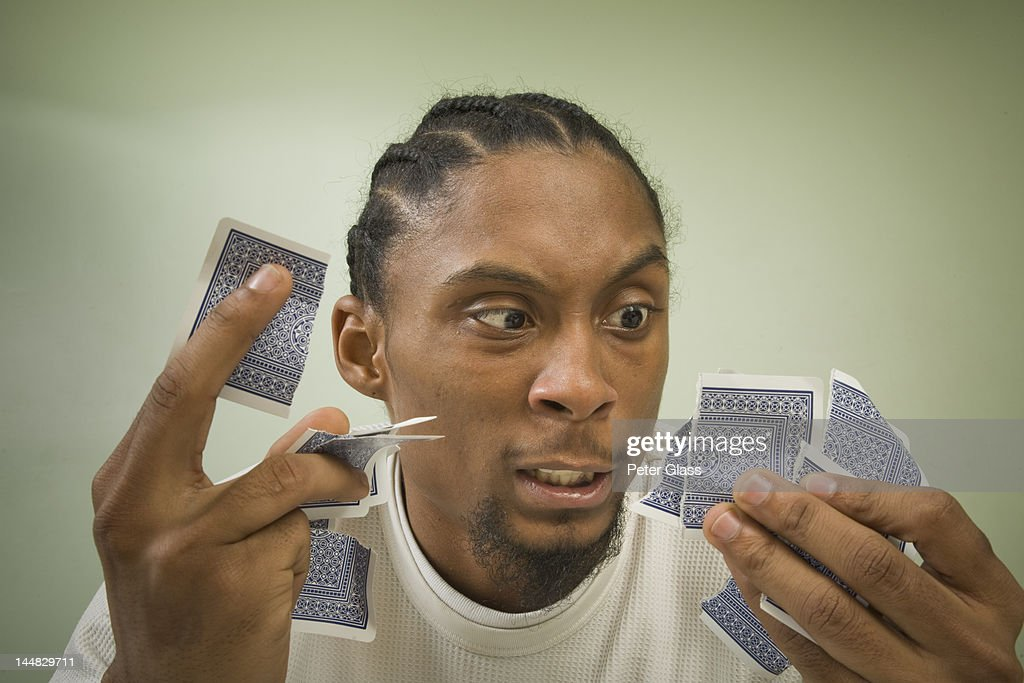 Black man with torn playing cards. : Stockfoto