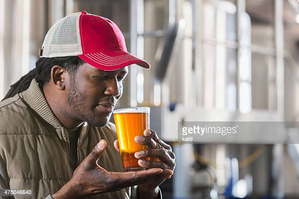 Black man working in a small brewery tasting beer