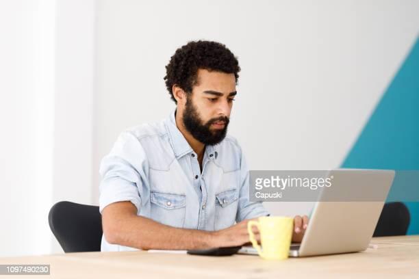 homem negro trabalhando no laptop - surfando na net - fotografias e filmes do acervo