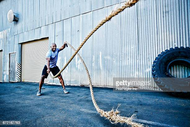 black man working out with heavy ropes outdoors - seil stock-fotos und bilder